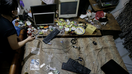 In this April 20, 2017, file photo, members of the National Bureau of Investigation and FBI gather evidence at the home of suspected child webcam cybersex operator, David Timothy Deakin, from Peoria, Ill., during a raid in Mabalacat, Philippines.