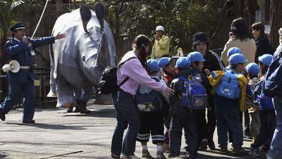 School children run from an escaped 'rhino' that escaped following a supposed earthquake in February, 2014 at Ueno Zoo in Tokyo.