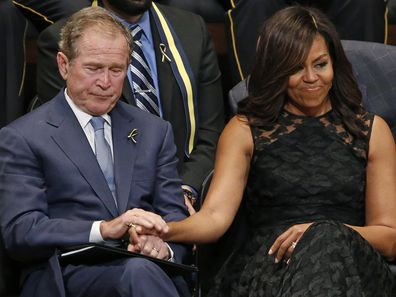 Michelle Obama holds former President George Bush's hand at memorial for five Dallas and DART police officers shot to death in 2016
