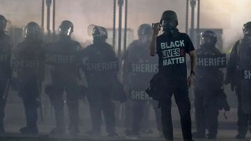 A protester holds up a phone as he stands in front of authorities in Kenosha, Wisconsin.