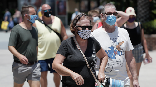 Guests required to wear masks because of the coronavirus pandemic stroll through the Disney Springs shopping, dining and entertainment complex Tuesday, June 16, 2020, in Lake Buena Vista, Fla. Walt Disney World Resort theme parks plan to reopen on July 11.(AP Photo/John Raoux)