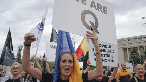 Romanian supporters of QAnon shout slogans against the government's measures to prevent the spread of the COVID-19 infections, like wearing a face mask, during a rally in Bucharest, Romania.