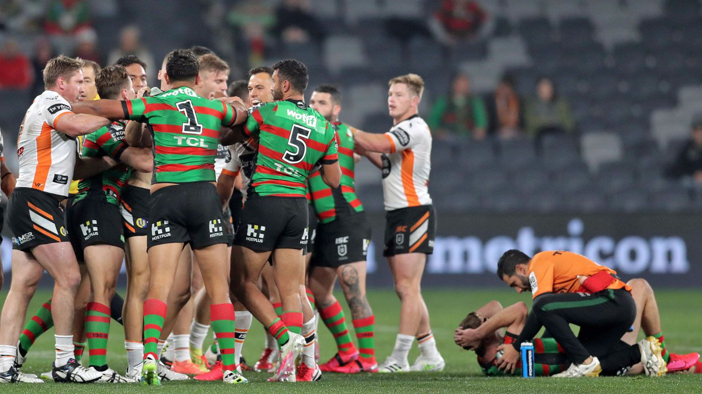 Players wrestle after Josh Reynolds of the Tigers kicks Campbell Graham of the Rabbitohs