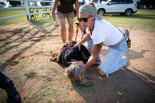 Police allege the woman has suffered suspected spinal injuries after a man allegedly knocked her over during a horseback anti-Adani protest in central Queensland.