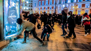 Demonstrators broke a glass during clashes with the police following a protest condemning the arrest of Mr Hasel in Madrid, Spain.