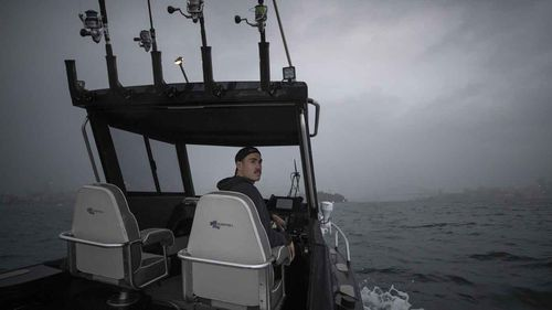 Greater Western Sydney Giants AFL player Jeremy Cameron drives his boat while out fishing on Sydney Harbour.