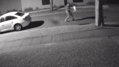 The man is seen running from a white Holden Cruze ... (Supplied)