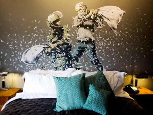 """A Banksy wall painting showing Israeli border policeman and Palestinian in a pillow fight is seen in one of the rooms of """"The Walled Off Hotel"""". (AAP)"""