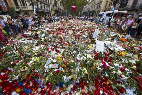 Flowers and candles are placed in tribute to victims of the terrorist attack in Las Ramblas boulevard in Barcelona. (AAP)