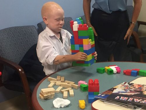 Baraka, 7, uses his new prosthetic to stack blocks. (Image: ABC News America)