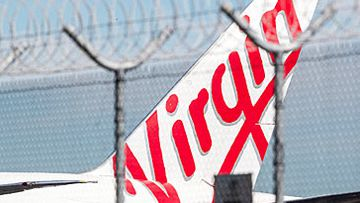 Virgin Australia jet behind razor wire (Getty)