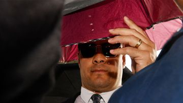 Jarryd Hayne was shielded by umbrellas when he arrived at Newcastle District Court today.