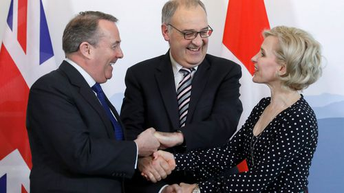 British Secretary of State for International Trade Liam Fox, Swiss Federal Councillor Guy Parmelin and Liechtenstein's Foreign Minister Aurelia Frick shake hands after signing a trade agreement in Bern, Switzerland.