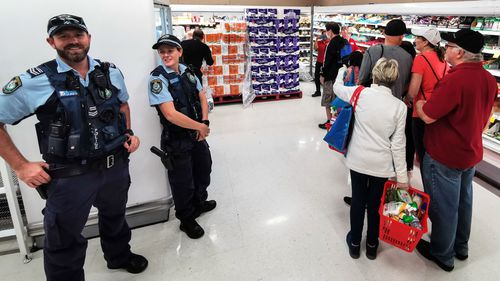 Police Officers watch as people queue for a delivery of toilet paper, paper towel and pasta at Coles Supermarket, in Sydney during March, 2020.