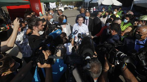 U.S. Undersecretary of State for Political Affairs David Hale, center, speaks to journalists as he visits the main gathering point for NGO volunteers, near the site of last week's explosion that hit the seaport of Beirut, Lebanon, Thursday, Aug. 13, 2020