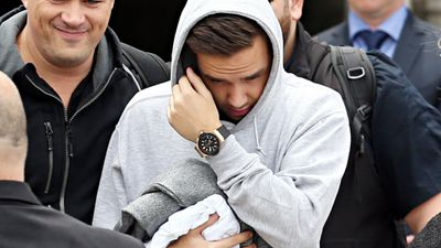 Liam Payne of One Direction shies away from hundreds of waiting fans as he arrives in Sydney on Tuesday. (Getty)