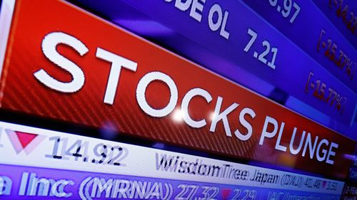 A television screen on the floor of the New York Stock Exchange headlines market activity