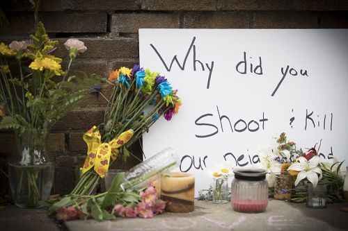 A placard outside Justine's house sums up the incomprehension of the locals to the shooting. Picture: AAP