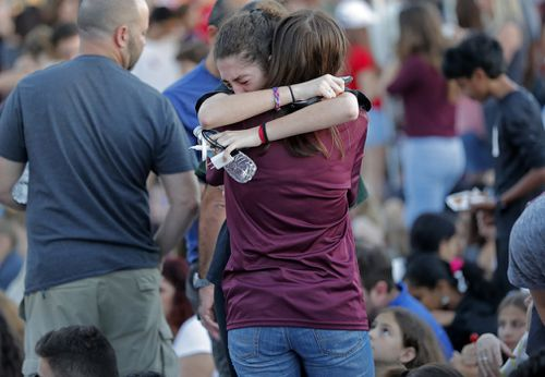 Students share an embrace at a memorial for the victims. (EPA/AAP)