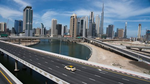 In this file photo from April 2020, a lone taxi cab drives over a highway in front of the Dubai skyline.
