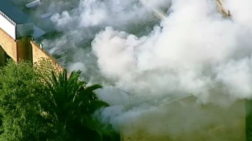 Smoke billowed from the property hours after the fire was extinguished. (9NEWS)