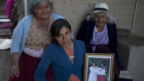 In this Aug. 23, 2018 photo, 117-year-old Julia Flores Colque Julia Flores Colque, behind right, poses for a photo with her grandniece Agustina Berna, left, and her great-grandniece Rosa Lucas
