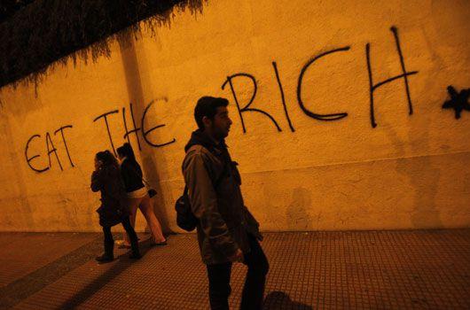 Pedestrians walk past graffiti in Athens. (AAP)