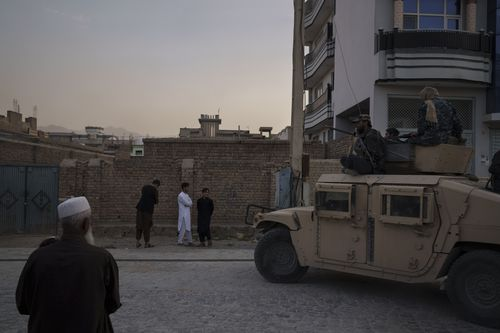 Afghans watch as Taliban fighters ride atop a humvee after detaining four men who got involved in a street fight in Kabul, Afghanistan