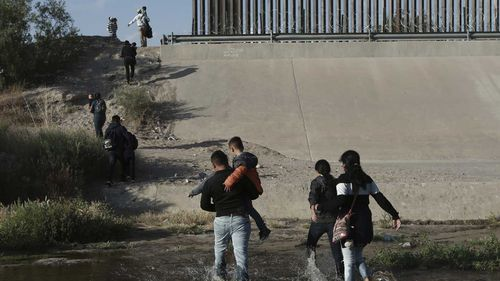 Migrants walk across the Rio Grande River to enter the US at El Paso, Texas.