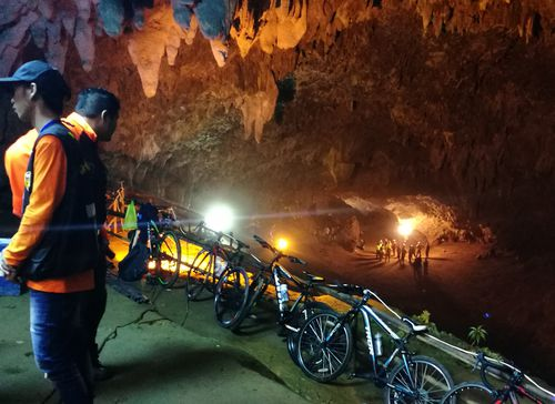 Thai rescue workers and park officials rest outside the Tham Luang Nang Non cave. Picture: AAP
