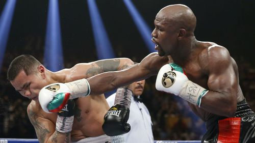 Floyd Mayweather Jr, right, connects with a right to the head of Marcos Maidana during a 2014 bout. (AAP)