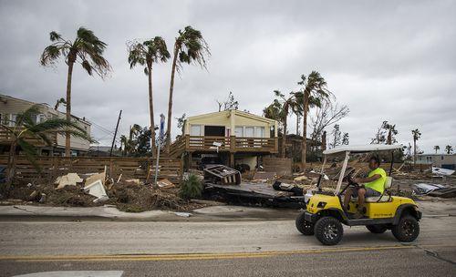 A man drives by debris cluttered properties in Port Aransas, Texas. (AP)