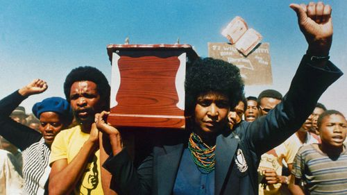 Winnie Mandela carries the coffin of activist William Kotoyi at his funeral in Brandfort, South Africa in 1986.(AP).