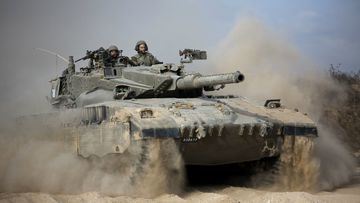 An Israeli tank moves into position on the Gaza border. (AAP)