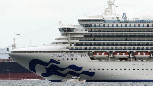 A small boat navigates near a cruise ship Diamond Princess anchoring off the Yokohama Port in Yokohama, near Tokyo.