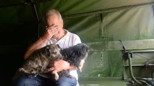 A handout photo made available by the Texas Military Department shows a resident reacting after being rescued with his pets from severe flooding in Cypress Creek, Texas. (AAP)