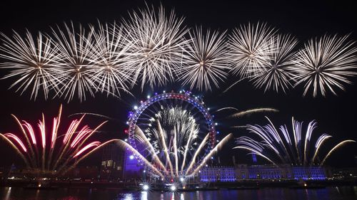 Fireworks explode over the London Eye Ferris wheel by the River Thames in London, to mark the start of the new year, Wednesday, Jan. 1, 2020