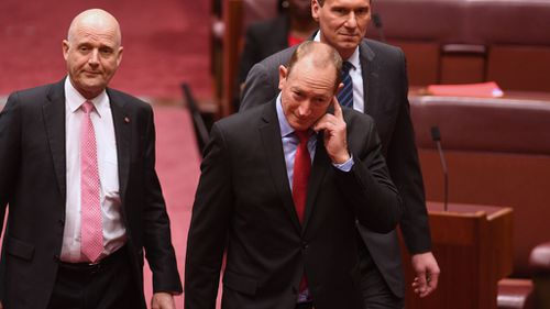 New Queensland Senator Fraser Anning (centre), who replaces former One Nation Senator Malcolm Roberts, arrives to be sworn-in in the Senate chamber (Image: AAP)