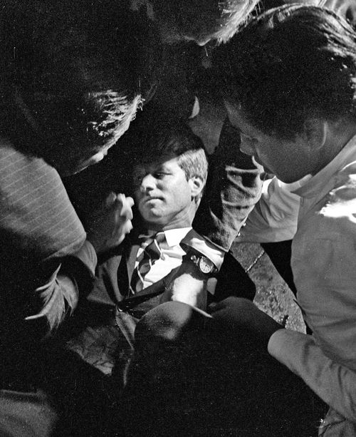 Hotel busboy Juan Romero, right, comes to the aid of Senator Robert F. Kennedy, as he lies on the floor of the Ambassador hotel in Los Angeles moments after he was shot