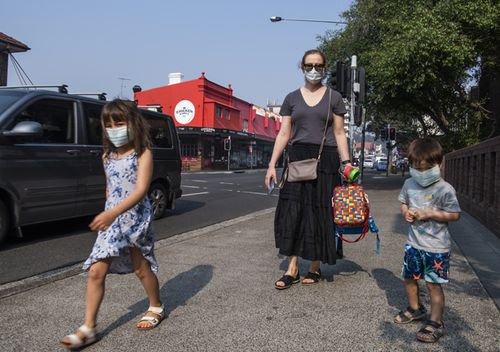 A Sydney mother and her two children wear face masks as they walk near Bondi, in Sydney's east.