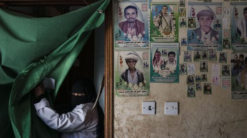 A face stares from behind a makeshift curtain, scenes from Yemen.
