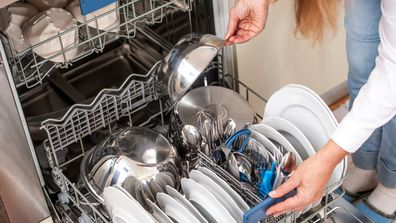 Unloading Dishwasher In The Kitchen