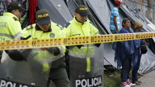 Police stand guard at a makeshift migrant settlement near the main bus terminal in Bogota, Colombia.