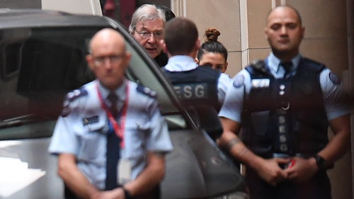 Cardinal George Pell (second from left) arrives at the Supreme Court of Victoria