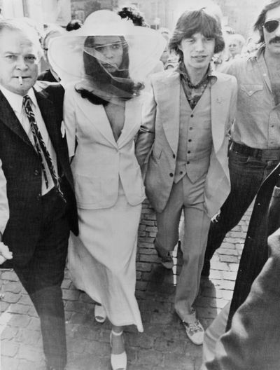"""<p>Bianca and Mick Jagger, 1971<br> Bride's suit: Tommy Nutter<br> <br> """"I had a very clear idea of what I wanted as a wedding dress,"""" Bianca says in the book <em>Fifty Fashion Looks that Changed the 1970s</em>. """"Contrary to popular opinion it wasn't a trouser suit; it was a long, narrow skirt and a jacket.</p> <p>""""He [tailor Tommy Nitter] made the wide-brimmed hat with a veil and we decided that instead of carrying a bouquet I should wear a flower corsage on my wrist to go with the suit.""""</p> <p>Because Bianca was four months pregnant she went without the blouse she had intended to wear because it no longer fitted.<br> <br> </p>"""