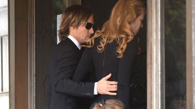 Keith Urban gently guides his wife, Nicole, into the church for the funeral service of her father, Dr Antony Kidman, in Sydney.