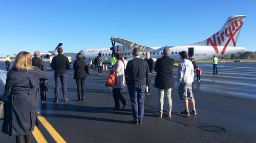 Passengers were evacuated from the flight, jumping from windows into the arms of waiting police officers. (AAP)