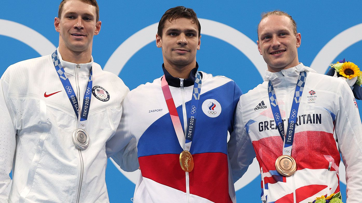 Silver medallist Ryan Murphy of Team United States, gold medallist Evgeny Rylov of Team ROC and bronze medallist Luke Greenbank of Team Great Britain pose on the podium during the medal ceremony for the Men's 200m Backstroke Final at the Tokyo Olympics.