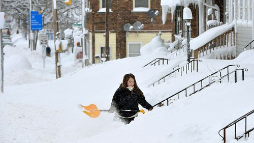 People are forced to clear their steps to avoid being snowed in. (Image: AAP)