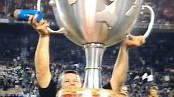 All Blacks captain Sean Fitzpatrick struggles to hoist the original, oversized Tri Nations trophy.